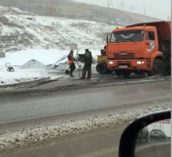 В Красноярске рабочие уложили асфальт на дорогу в снег и грязь